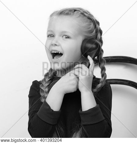 Happy Girl Talking By Old Telephone. Black And White Portrait Of Smiling Lovely Kid Sitting On Chair