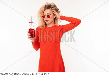 Handsome Young Caucasian Female With Short Curly Fair Hair In Red Sunglasse In Red Blouse Drinks Red