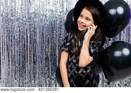 Teenager Girl Talking On The Phone At A Party Among Black Helium Balloons And Tinsel With Copy Space