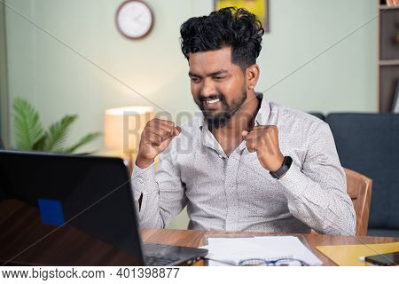 Young Man Reading Mail On Laptop Got Overjoyed By Good News By Clenching Fist At Workplace - Concept