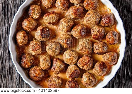 Meatballs Of Ground Beef And Ground Pork Baked In The Oven Served On A Baking Dish, On A Dark Wooden
