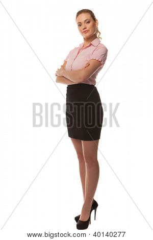 Stylish businesswoman in a summer outfit and stillettoes posing with her arms crossed, full length portrait isolated on white