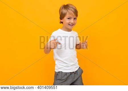 Portrait Of Beautiful Young Caucasian Boy In White T-shirt And Grey Trousers Shows Himself And Smile