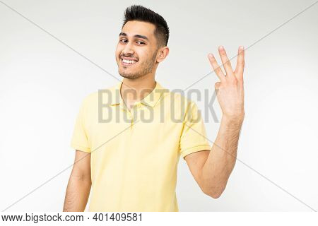 Caucasian Man In A Yellow T-shirt Shows Three Fingers On A White Isolated Background.