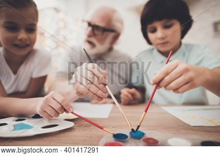 Grandfather, Grandson And Granddaughter At Home. Children Are Painting.