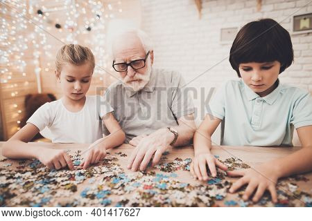 Grandfather, Grandson And Granddaughter At Home. Grandpa And Children Are Playing With Puzzles.