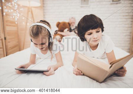Grandfather, Grandson And Granddaughter At Home. Children Are Listening To Music And Reading While G