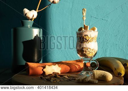 Biscuits, Bananas, Yoghurt And Muesli In A Glass And Muesli Sprinkled A Little On The Table, On The