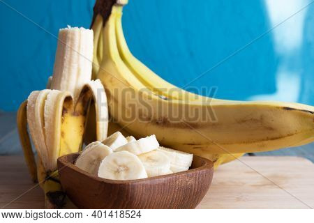 Bananas Lie On The Board, Whole And Bitten Banana, Next To The Banana Slices In A Wooden Cup, On The