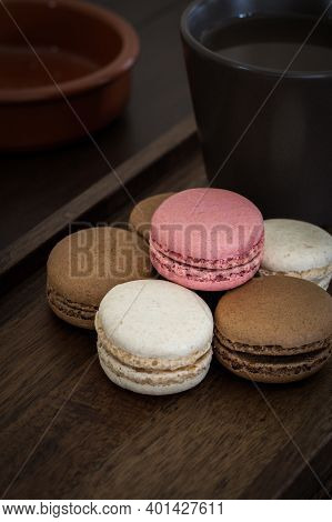 A Close Up Of Delicious Sweet Macarons With A Hot Cup Of Coffee On A Wooden Background For A Cozy Sn