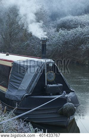 Bath, Somerset, United Kingdom - December 31, 2020: Smoke From The Chimney Of A Narrowboat On A Fros