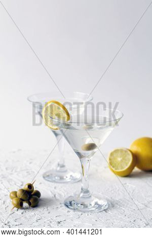Margarita Cocktail In The Bar. Two Martini Glasses Of Cocktail With Green Mint And Olives On White B