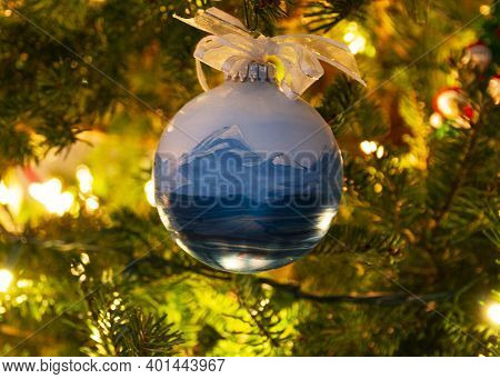 A Round Christmas Tree Ornament Hanging From A Christmas Tree With Lights On In The Background.