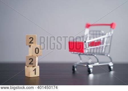 Text 2021 On Wooden Cube With Shopping Cart.