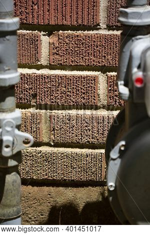 Dingy Red Brick Wall Between A Water Meter And Water Meter Pipe