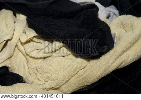 Close Up Of Dirty Yellow And Black Towels And Colorful Wash Cloths On The Floor