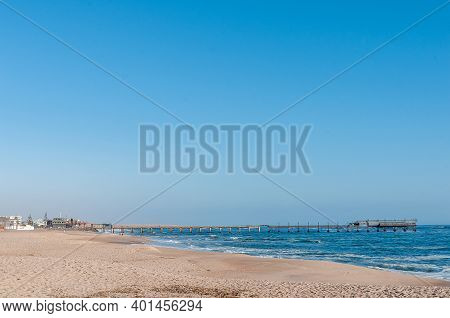 Swakopmund, Namibia - June 18, 2012: A Beach Scene, With The Historic Jetty From The German Era, In