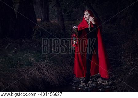 Attractive Woman Dressed A Little Red Riding-hood Cross Stream In A Dark Forest With A Lantern