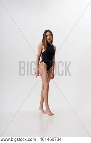 Sexy Asian Woman With Long Hair Posing In Black Lingerie On White Studio Background With Bare Feet.