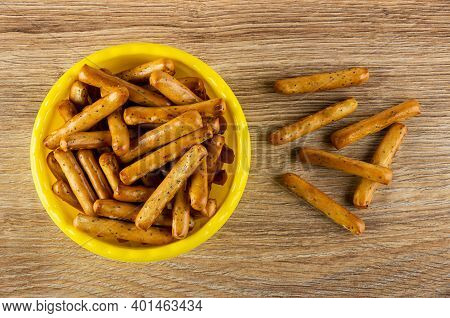 Breadsticks With Poppy In Yellow Plastic Bowl, Breadsticks On Brown Wooden Table. Top View
