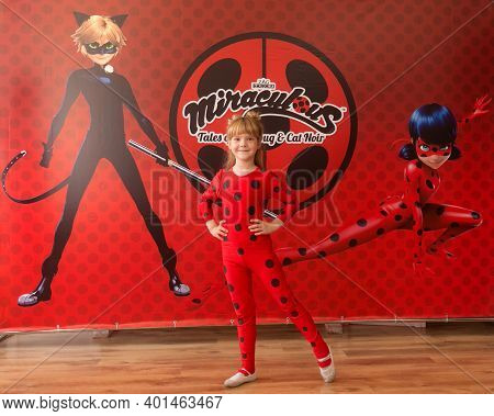 Lutsk, Ukraine - June 10 2019: Little Girl In Ladybug Myraculous Cosplay Costume Posing Next To Bann