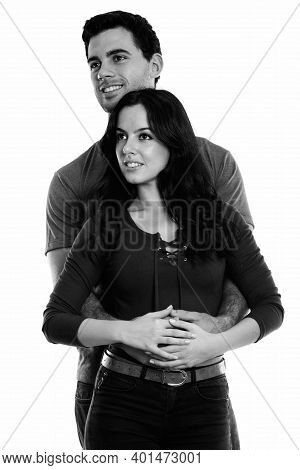 Studio Shot Of Thoughtful Young Happy Couple Smiling While Hugging Each Other