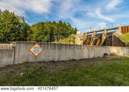 Large Rural Dam. Large Concrete Dam With Sign Warning Of Rising Water Levels. Located In Baraga Coun