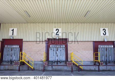 Truck Loading Docks At Commercial Building. Overhead Door, Dock Leveler, And Dock Seals