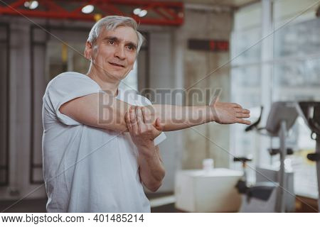 Healthy Senior Man Stretching His Shoulders And Arms Before Workout At The Gym. Cheerful Elderly Man