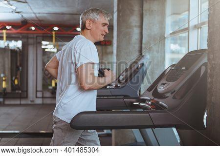 Senior Sportsman Running On A Treadmill At The Gym, Copy Space. Healthy Elderly Man Enjoying Working