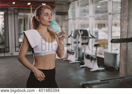 Gorgeous Athletic Woman Drinking Water At The Gym After Exercising. Beautiful Healthy Female Athlete