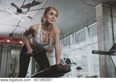 Low Angle Shot Of A Gorgeous Athletic Woman Lifting Weights At The Gym, Copy Space. Attractive Sport