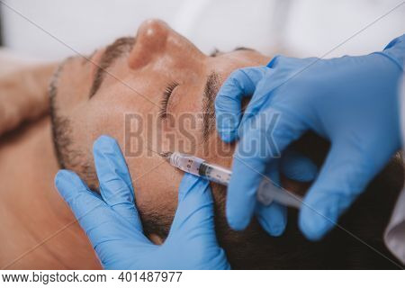 Cropped Close Up Of A Professional Cosmetologist Doing Face Filler Injections At Work. Mature Man Re