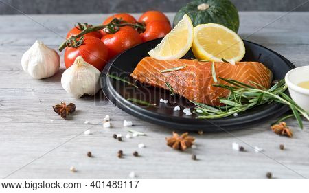 Grilled Salmon Steak On Vintage Wooden Board With Fork, Olive Oil, Vegetables, Herbs And Spices On D