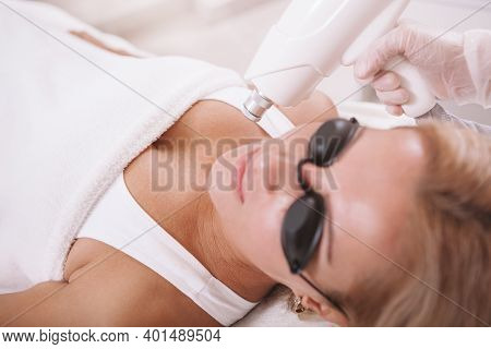 Professional Dermatologist Removing Skin Pigmentation On A Mature Female Patient. Woman Getting Lase