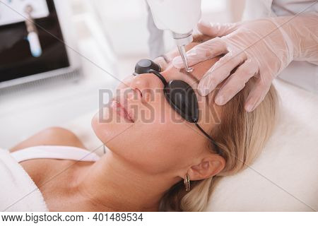 Close Up Of A Mature Woman Getting Her Tattooed Eyebrows Removed With Laser. Dermatologist Removing