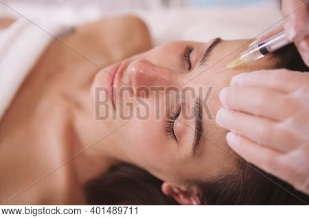 Close Up Of A Woman Getting Anti-wrinkle Filler Injections In Her Forehead. Female Client Receiving