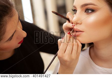 Professional Makeup Artist Painting Lips Of A Female Client. Fashion Model Getting Ready For Runway