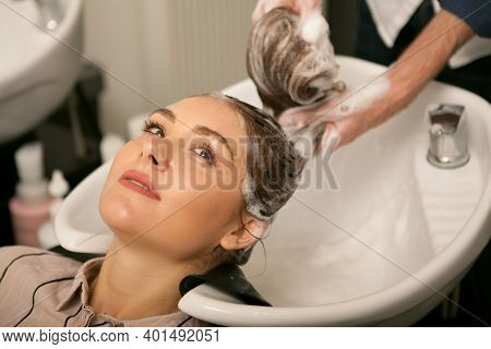 Cropped Shot Of A Young Lovely Woman Smiling Looking Away, While Professional Hairstylist Washing He
