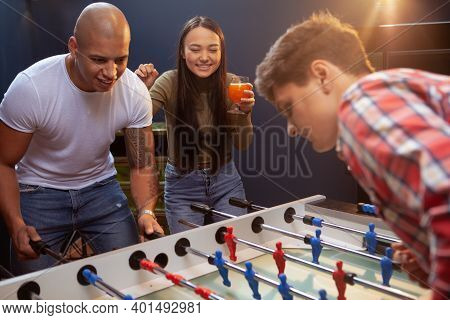 Beautiful Young Asian Woman Cheering Her Friends During Table Football Match. Happy Friends Playing