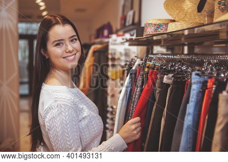 Beautiful Cheerful Woman Smiling To The Camera While Shopping For New Clothes At Fashion Store, Copy