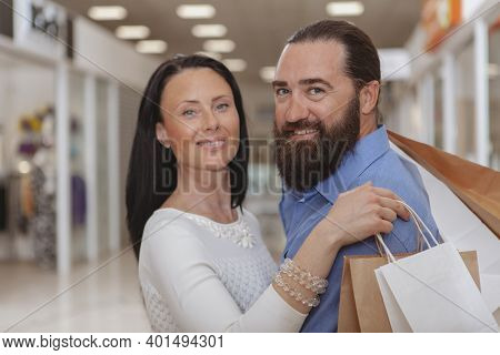 Bearded Handsome Mature Man Hugging His Gorgeous Wife, Smiling To The Camera At The Shopping Mall. H