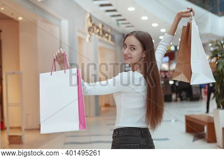 Gorgeous Long Haired Woman Smiling To The Camera Over Her Shoulder, Holding Up Shopping Bags, Walkin