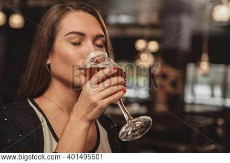 Close Up Of A Gorgeous Young Woman Enjoying Drinking Delicious Beer At The Restaurant. Beautiful Wom