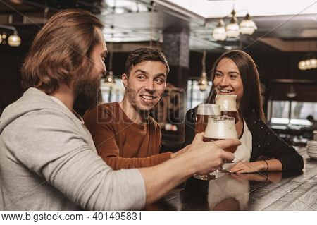 Group Of Friends Enjoying Celebrating At The Local Pub, Chatting Happily, Drinking Beer Together. Ha