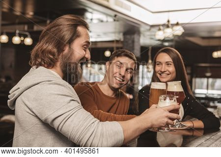 Group Of Happy Friends Clinking Their Beer Glasses, Laughing Joyfully, Celebrating At The Irish Pub.