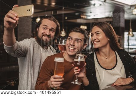 Group Of Friends Having Fun At Beer Pub Together, Taking Selfies With Smart Phone. Bearded Cheerful