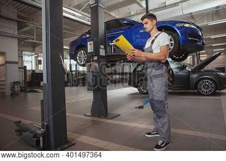 Full Length Shot Of A Young Male Car Mechanic Holding Clipboard, Standing In Front Of A Car On The L