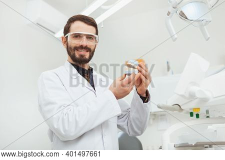 Charming Mature Male Dentist Smiling To The Camera, Holding Dental Mold, Copy Space. Happy Dentist E