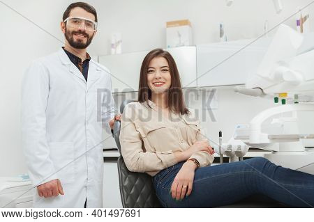 Cheerful Young Woman And Her Dentist Smiling To The Camera After Medical Examination At Dental Clini